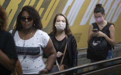 Moradoras de São Paulo usando máscara no metrô.