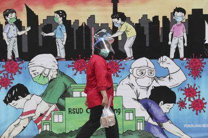 Um funcionário passa por um mural com o tema do coronavírus em homenagem aos trabalhadores de saúde do Hospital Geral Regional de Cengkareng em Jacarta, na Indonésia.