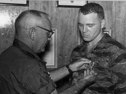 """Bo Gritz recebe uma de suas medalhas pela coragem em combate. Entre as coisas que fez quando se aposentou estava organizar milícias com este lema: """"indivíduos especialmente preparados para situações-chave""""."""