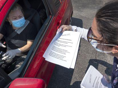 Uma funcionária distribui formulários para solicitar o seguro-desemprego na Flórida.