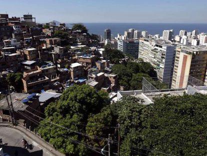 Vista de uma favela ao lado de modernos edifícios no Rio de Janeiro.