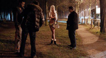 Dois agentes interrogam prostituta e cliente durante operação policial