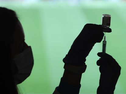 Enfermeiro segura uma seringa de injeção e uma ampola com a vacina contra a covid-19 em um centro de vacinação instalado no Estádio Wanda Metropolitano, em Madri, nesta terça-feira.