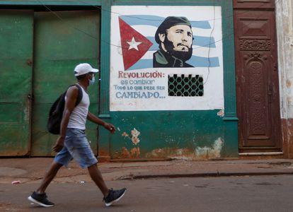 Homem passa por grafite de Fidel Castro em Havana na sexta-feira.