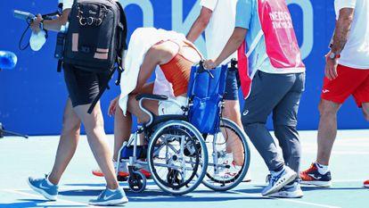 Paula Badosa sai da quadra de Tóquio em uma cadeira de rodas.