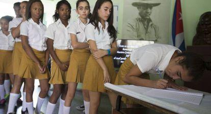 Estudantes assinam o livro de condolências de Fidel Castro.
