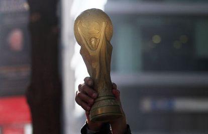 Um torcedor segura uma réplica da Copa do Mundo.