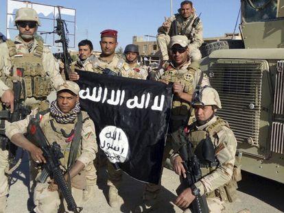 Soldados iraquianos exibem uma bandeira do Estado islâmico na província de Anbar.