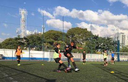 Ana Julia disputa a bola com um colega de equipe.