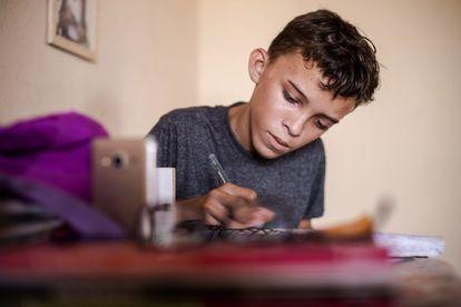 Maycon de Oliveira realiza as tarefas escolares com o auxílio de um celular, no Ceará.