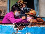 Una familia en Pamplona Alta, a las afueras de Lima (Perú), se prepara para salir con mascarillas.