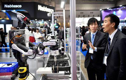 Dois participantes observam um robô industrial em uma feira de robótica em Tóquio.