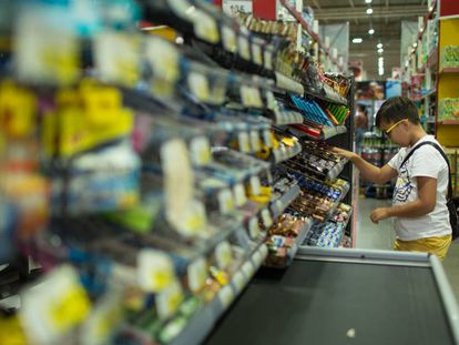 Menino na seção de doces de um supermercado.