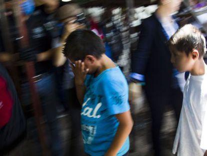 Um menino chora antes de ser levado para a sua cidade natal.