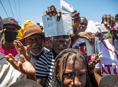 Cidadãos haitianos mostram seus passaportes para pedir asilo em frente à embaixada dos Estados Unidos em Tabarre, neste sábado.