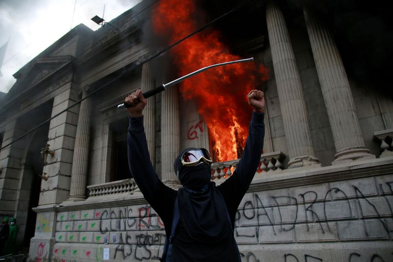 Um homem protesta em frente ao Congresso da Guatemala, que foi incendiado por alguns manifestantes.