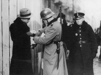 Soldados alemães e membros da Polícia Azul controlam a entrada do Gueto de Varsóvia em 1941.