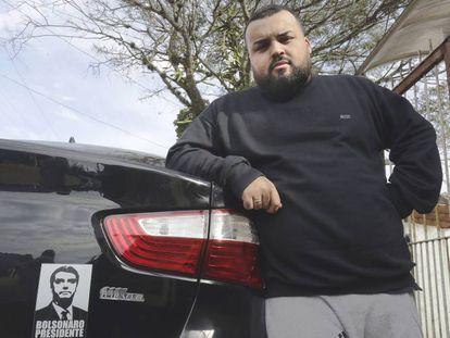 Anriel do Prado Neves, de 24 anos, mostra o adesivo de Jair Bolsonaro no carro que dirige para um aplicativo.