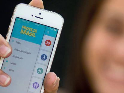 Jovem segura celular com o 'app' do Proteja Brasil.