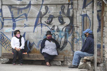 Três pessoas se protegem do vírus com máscaras, em julho passado, em Quito (Equador).