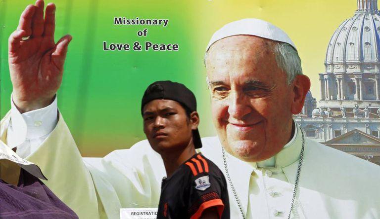 Um homem passa diante de um anúncio da viagem do Papa em Yangon.