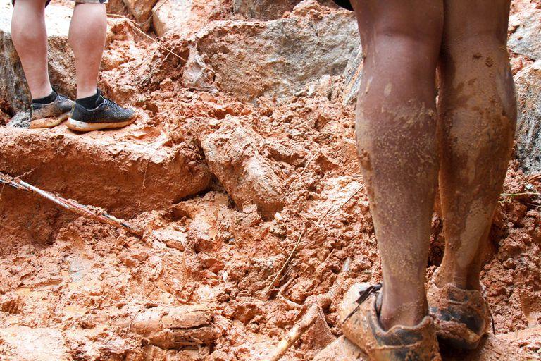 Pessoas caminham sobre área destruída pela chuva no Morro do Macaco Molhado, em Guarujá (SP).