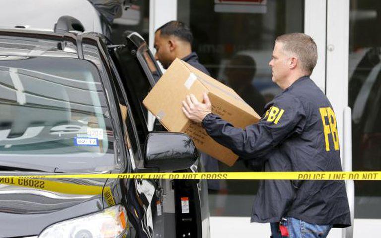 Agentes do FBI saem com caixas da sede da Imagina, em Miami.