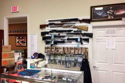 Várias escopetas em uma parede da loja.