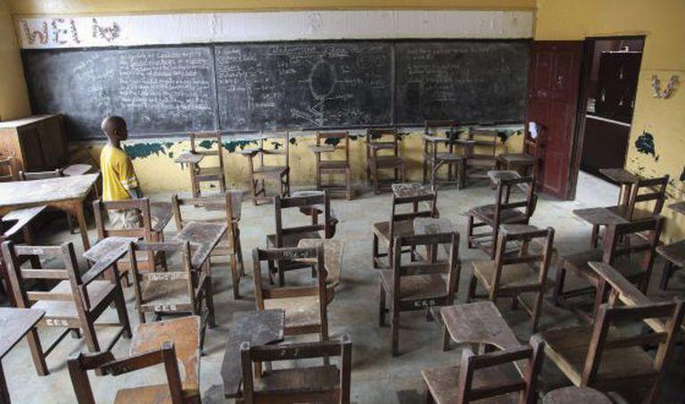 Um liberiano caminha em uma escola fechada em Monrovia.