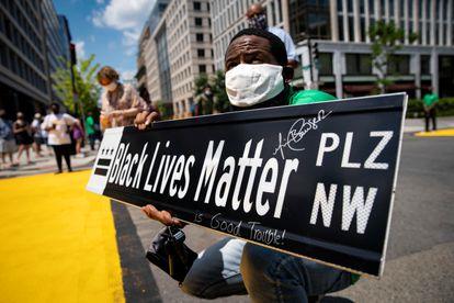 """Um homem exibe um cartaz com o novo nome da rua 16, 'Black Lives Matter Plaza' (""""Praça Vidas Negras Importam"""")."""