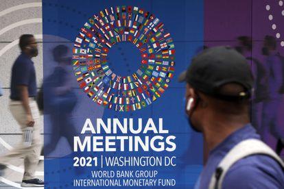 Um homem passa por um cartaz das reuniões anuais do Grupo do Banco Mundial e do Fundo Monetário Internacional, nesta segunda-feira, em Washington.