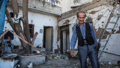 Um membro das forças de segurança curdas inspeciona uma casa bombardeada nesta terça-feira em Qamishli.