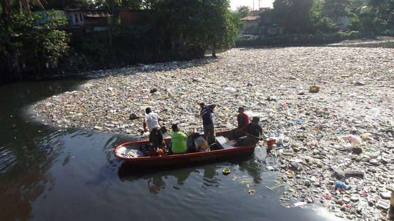 Um grupo de cidadãos retira plásticos de um rio nas Filipinas