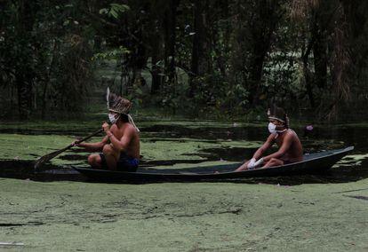 Indígenas com máscaras navegam pelo rio Ariaú, a 80 quilômetros de Manaus.