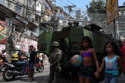 Duas meninas caminham ao lado de uma viatura militar.