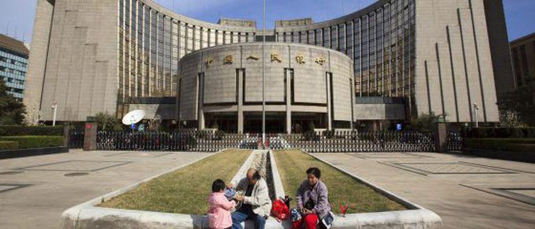 Uma família em frente ao Banco Popular da China, em Pequim.