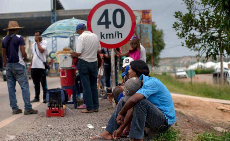 Refugiados venezuelanos formam fila em ponto de imigração brasileiro.