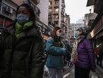 People walk along a street near a market in Wuhan, China's central Hubei province on January 19, 2021. (Photo by Hector RETAMAL / AFP)