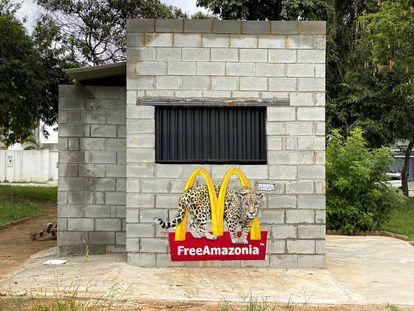 """Grafite com uma onça passando pelo logo da lanchonete McDonald's, escrito """"Libertem a Amazônia"""", em Goiânia."""