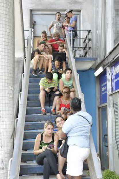 Usuários de WiFi público em uma escada do hotel Havana Livre.