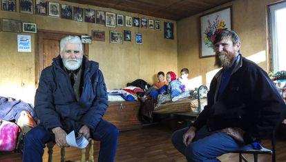 Fedor Kronikovski (à esquerda) conversa com Ulian Murashov (à direita). Ao fundo, os dois filhos da família, Agripina e Filaret, junto a outra criança.