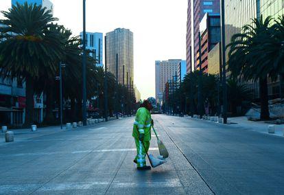 Trabalhador limpa rua vazia na Cidade do México.