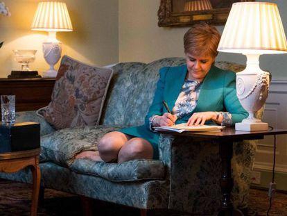 Imagem cedida pelo Governo escocês que mostra a Sturgeon trabalhando na carta a Maio
