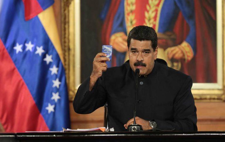 Maduro exibe exemplar da Constituição venezuelana durante discurso.