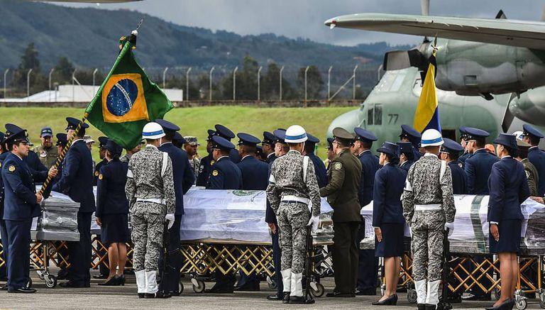 Militares colombianos preparam a partida de caixões das vítimas ao Brasil.