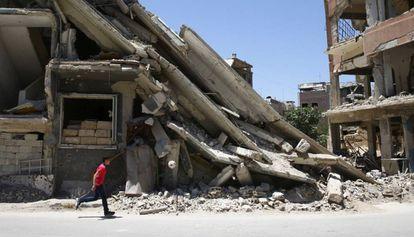 Um menino brinca em frente a um edifício destruído em Damasco.