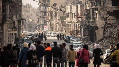 Um grupo de pessoas caminha por uma rua de Homs.