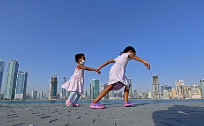 Meninas caminham à beira-mar no distrito de al-Mamzar, em Dubai, em 14 de maio, após flexibilização das medidas de bloqueio da pandemia.