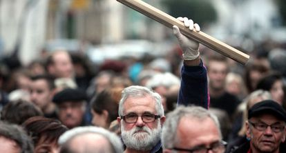Homem segura lápis gigante durante uma manifestação na França.