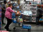 Shoppers stand in line inside a large warehouse retailer, Thursday, March 12, 2020, in Kennesaw, Ga. Amid all the fears, quarantines and stockpiling of food, it has been easy to ignore the fact that more than 60,000 people have recovered from the coronavirus spreading around the globe. (AP Photo/Mike Stewart)